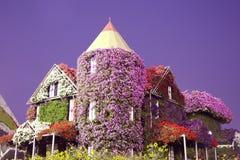 Een reusachtig bloembed in de vorm van het mirakeltuin van het plattelandshuisjehuis