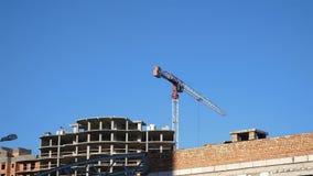 Een reusachtig stationair hijstoestel zet snel de achtergrond van een blauwe hemel dichtbij het onlangs gebouwde gebouw aan stock video