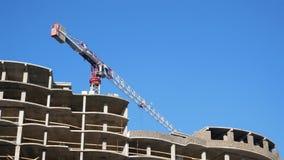 Een reusachtig stationair hijstoestel zet snel de achtergrond van een blauwe hemel dichtbij het onlangs gebouwde gebouw aan stock footage