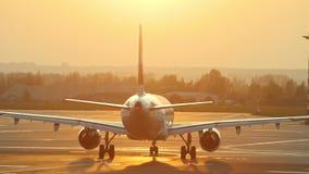Een reusachtig vliegtuig beweegt zich op de luchthavenbaan op een achtergrond van oranje zonsondergang stock footage