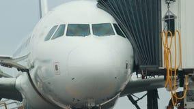 Een reusachtig vliegtuig die zich op het vliegtuiggebied bevinden Een overgangspas met wordt verbonden gaat in het vliegtuig dat  stock videobeelden