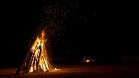 Een reusachtig vuur op het zand en een kleine brand op de achtergrond Veel vonken stock video
