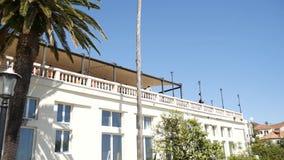 Een reusachtig wit landgoed met meerdere verdiepingen in palmen Herceg Novi, Mon stock videobeelden