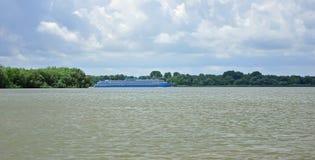 Een reusachtige boot gaat op de brede rivier Donau tegen de blauwe hemel stock fotografie