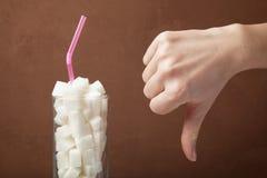 Een reusachtige hoeveelheid suiker in sap of sodadranken De suiker kubeert in glas en de hand toont neer duimen stock foto's