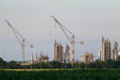 Een reusachtige olieraffinaderij met kranen in aanbouw Stock Afbeelding