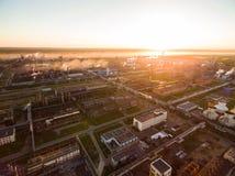 Een reusachtige olieraffinaderij met metaalstructuren, pijpen en distillatie van het complex bij zonsondergang Lucht Mening stock foto's
