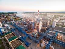 Een reusachtige olieraffinaderij met metaalstructuren, pijpen en distillatie van het complex met het branden lichten bij schemer  royalty-vrije stock afbeeldingen