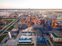 Een reusachtige olieraffinaderij met metaalstructuren, pijpen en distillatie van het complex met het branden lichten bij schemer  stock foto