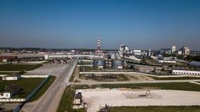 Een reusachtige olieraffinaderij met metaalstructuren, pijpen en distillatie van het complex met het branden lichten bij schemer  stock fotografie