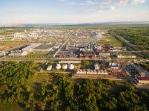 Een reusachtige olieraffinaderij met pijpen en distillatie van het complex op een groen die gebied door bos Luchtmening wordt omr stock foto's