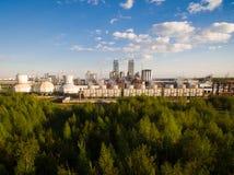Een reusachtige olieraffinaderij met pijpen en distillatie van het complex op een groen die gebied door bos Luchtmening wordt omr royalty-vrije stock fotografie