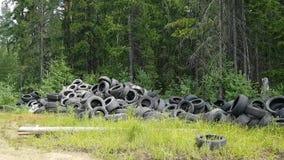 Een reusachtige onwettige stortplaats van oude banden en wielen in het hout ecologische crisisfoto Milieuproblemen in ontwikkelin stock footage