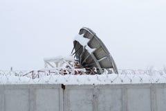 Een reusachtige satellietschotel is achter een grijze omheining met prikkeldraad royalty-vrije stock foto's