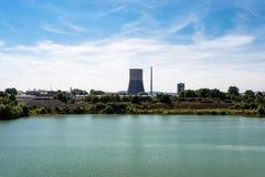 Een reusachtige schoorsteen van een kernenergieinstallatie in West-Duitsland, een turkoois waterreservoir, een blauwe hemel met w royalty-vrije stock foto's