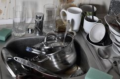 Een reusachtige stapel van ongewassen schotels in de keukengootsteen en op countertop Heel wat werktuigen en keukentoestellen vóó royalty-vrije stock afbeeldingen