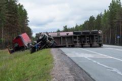 Een reusachtige wagen rolde over na een ongeval op de weg Scandi stock foto's