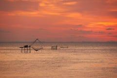 Een reuze vierkant netto visserij en een silhouet van een visser op longtailboot stock afbeeldingen