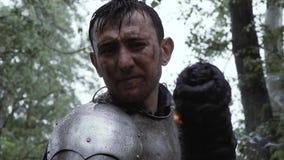 Een ridder in plaatpantser bevindt zich met een toorts in hand in het bos stock video