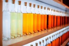Een rij van gekleurde flessen met cognac stock foto's