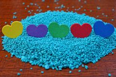 Een rij van gekleurde harten op blauw zand op een rode lijst Royalty-vrije Stock Afbeelding