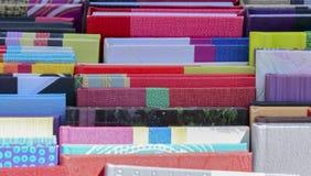 Een rij van gekleurde notitieboekjes in de markt stock foto's