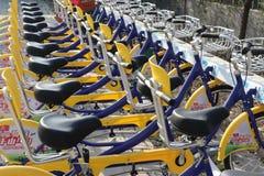 Een rij van gele fietsen deelde fietsen Stock Foto's