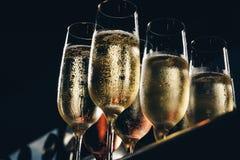 Een rij van glazen met champagne worden gevuld die is opgestelde klaar om worden gediend Stock Foto