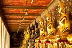 Een rij van gouden Boedha en zwarte Boedha Stock Afbeeldingen