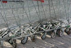 Een rij van grijze boodschappenwagentjes van een supermarkttribune op de straat royalty-vrije stock fotografie