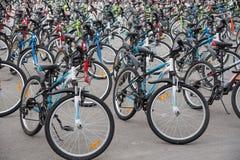Een rij van een groot aantal fietsen met wielen op stadssqua Stock Foto