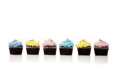 Een rij van pastelkleur cupcakes op een witte achtergrond Stock Fotografie