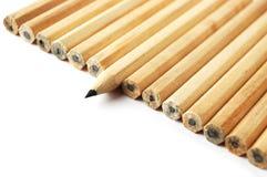 Een rij van potloden met in verschillende positie Stock Foto's