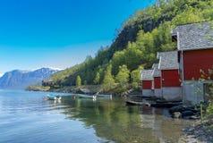 Een rij van rode plattelandshuisjes met kleine boten bij Flam-dorp royalty-vrije stock fotografie