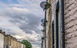Een rij van satellietschotels op terrasvormige huizen royalty-vrije stock afbeeldingen