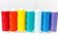 Een rij van spoelen van draad De Kleuren van de regenboog stock afbeeldingen