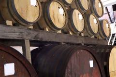 Een rij van wijnvatten in een wijnmakerijkelder stock afbeelding