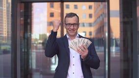 Een rijke jonge zakenman telt geld die zich dichtbij het commerciële centrum bevinden die een goede stemming hebben 4K stock footage