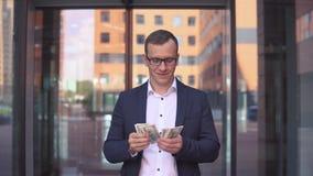Een rijke zakenman overweegt geld die zich dichtbij het commerciële centrum bevinden 4K stock footage