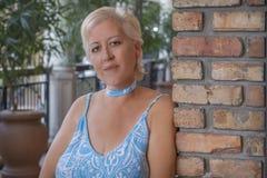 Een rijpe blonde vrouw leunt op een bakstenen muur bekijkend camera met een glimlach stock fotografie