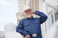Een rijpe cowboy in een hoed, jeans en een denimoverhemd bekijkt de camera op openlucht royalty-vrije stock fotografie
