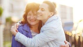 Een rijpe moeder en een volwassen dochter kwamen op de straat samen en omhelzen Gelukkige familie, continuïteit van generaties mo stock footage