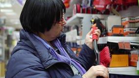 Een rijpe vrouw kiest een borstel met schraper in de supermarkt