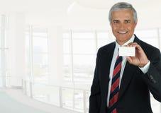 Een rijpe zakenman die in hoog zeer belangrijk bureau het houden van een leeg adreskaartje plaatsen royalty-vrije stock afbeeldingen
