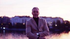 Een rijpe zakenman die zich op een brug in Praag bij schemer bevinden stock footage