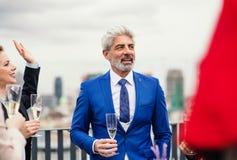 Een rijpe zakenman op een partij in openlucht op dakterras in stad royalty-vrije stock afbeelding