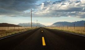 Een rijweg in een platteland met bergen stock afbeelding