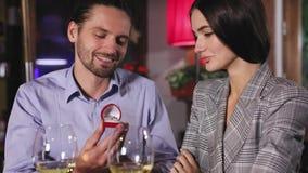 Een ring van de overeenkomstendiamant in boeket van rozen De man die vrouw voorstellen wordt gehuwd in restaurant stock video
