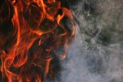 Een rituele dans van brand en rook tegen een achtergrond van groen gras Drie elementen Stock Afbeeldingen