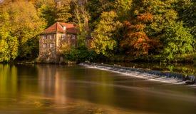 Een rivier kruist een waterkering, met een achtergrond van een huis & de herfstbomen royalty-vrije stock afbeelding